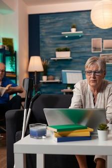 Senior vrouw die thuis naar laptop op de bank kijkt