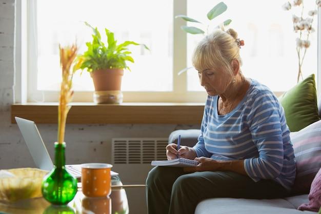 Senior vrouw die thuis studeert, online cursussen krijgt, zelfontwikkeling. blanke vrouw die moderne apparaten gebruikt om plezier te hebben, te leren, tijd door te brengen voor een nieuwe baan of hobby.