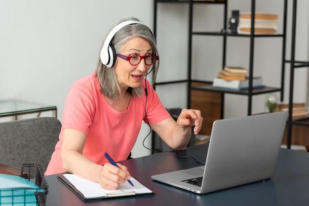 Senior vrouw die thuis studeert terwijl ze een laptop gebruikt en aantekeningen maakt