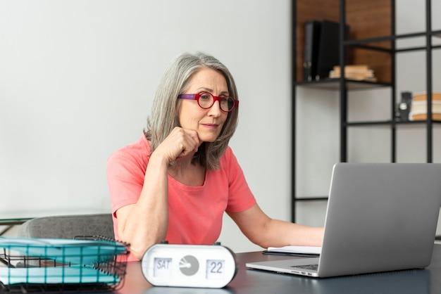 Senior vrouw die thuis studeert terwijl ze laptop gebruikt