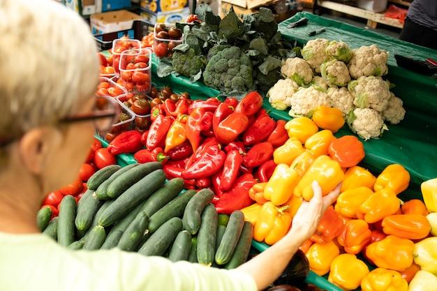 Senior vrouw die verse biologische groenten koopt op de markt en een tas vol gezond voedsel vasthoudt