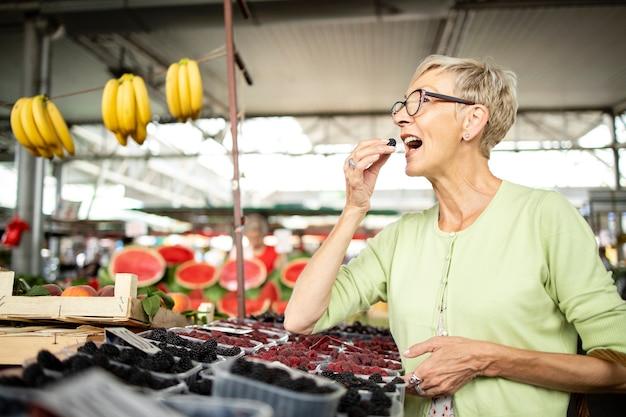Senior vrouw die verse bramen koopt op de markt en een zak vol gezond voedsel vasthoudt
