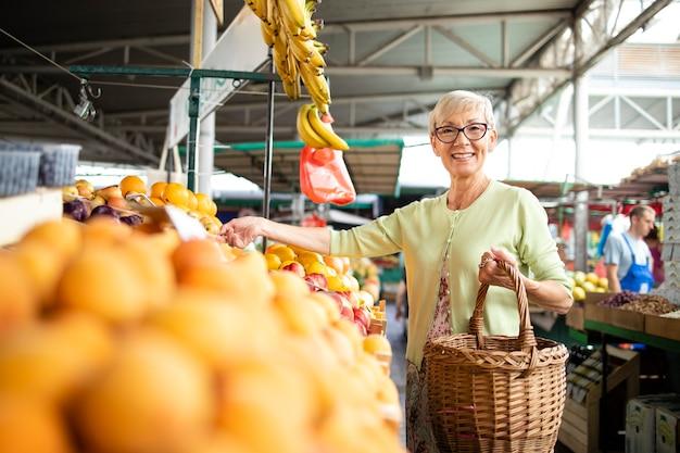 Senior vrouw die verse groenten en fruit koopt op de markt en een tas vol gezond voedsel vasthoudt