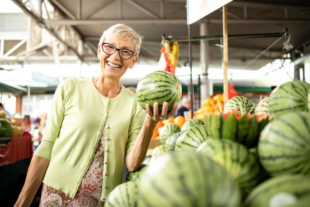 Senior vrouw die verse watermeloenen en fruit koopt op de markt en een tas vol gezond voedsel vasthoudt