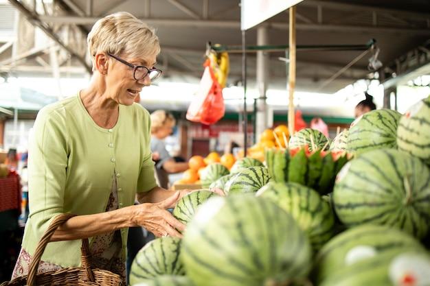 Senior vrouw die verse watermeloenen koopt op de markt en een zak vol gezond voedsel vasthoudt