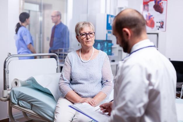 Senior vrouw die vragen van de arts beantwoordt tijdens onderzoek in de ziekenhuiskamer