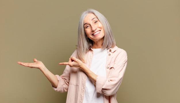 Senior vrouw die vrolijk lacht en wijst om ruimte op de palm aan de zijkant te kopiëren, een object te tonen of te adverteren or
