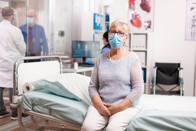 Senior vrouw die wacht op doktersoverleg in het ziekenhuis met gezichtsmasker in de loop van covid19