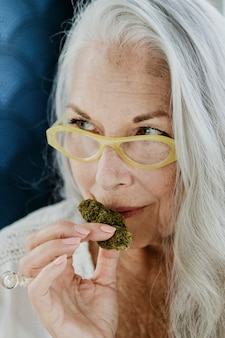 Senior vrouw die wiet ruikt