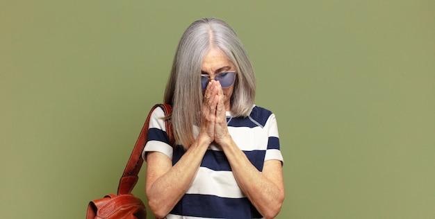 Senior vrouw die zich bezorgd, hoopvol en religieus voelt, trouw bidt met ingedrukte handpalmen