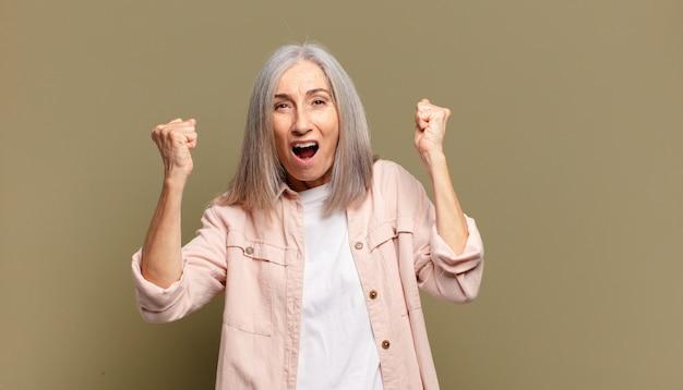 Senior vrouw die zich blij, verrast en trots voelt, schreeuwt en succes viert met een grote glimlach