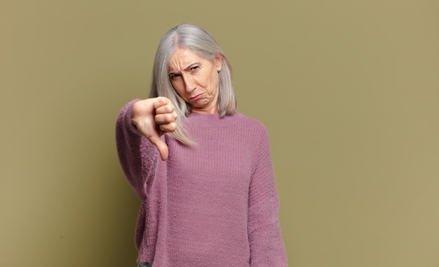 Senior vrouw die zich boos, boos, geïrriteerd, teleurgesteld of ontevreden voelt, duimen naar beneden laat zien met een serieuze blik