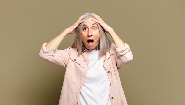 Senior vrouw die zich geschokt en geschokt voelt, haar handen opheft en in paniek raakt bij een fout
