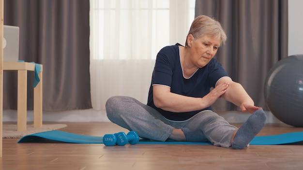 Senior vrouw die zich uitstrekt zittend op yoga mat in de woonkamer. actieve gezonde levensstijl sportieve oude persoon training workout thuis wellness en indoor training