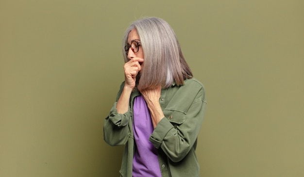 Senior vrouw die zich ziek voelt met keelpijn en griepsymptomen, hoesten met bedekte mond