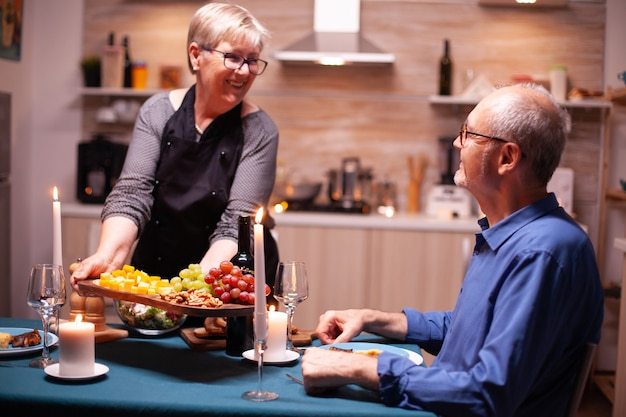 Senior vrouw dienende man met druiven en noten als aperitief voor een romantisch diner. bejaard oud echtpaar praten, aan de tafel in de keuken zitten, genieten van de maaltijd, hun jubileum vieren.