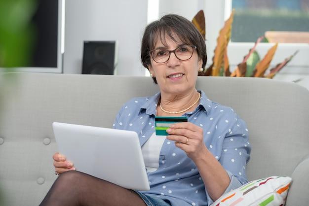Senior vrouw doet online winkelen