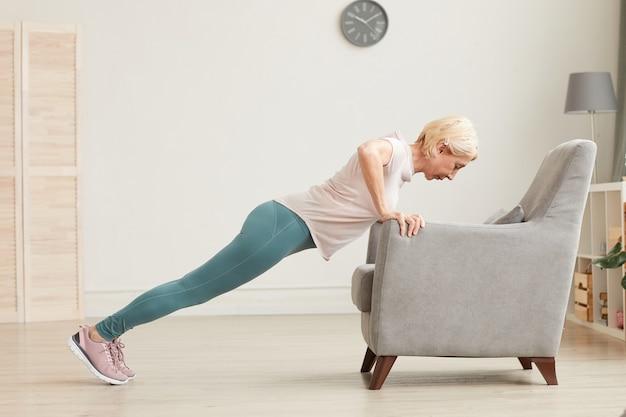 Senior vrouw doet push ups met behulp van fauteuil tijdens sporttraining thuis