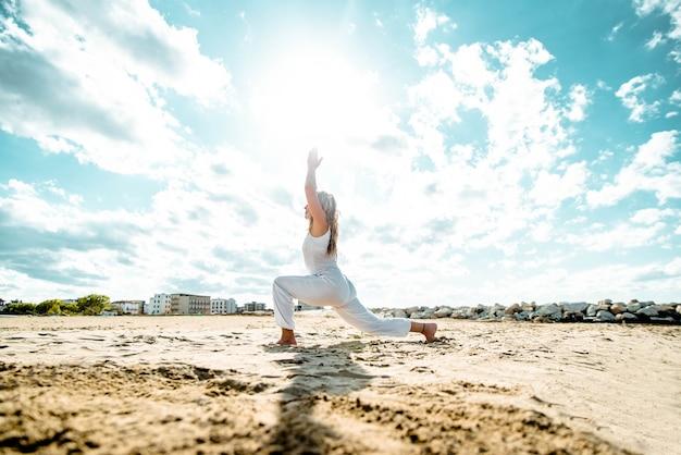 Senior vrouw doet yoga oefening boom pose op strand