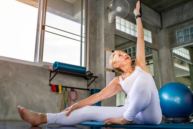 Senior vrouw doet yoga oefening op fitness gym.