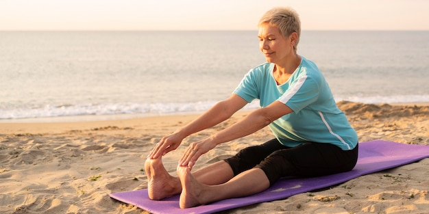 Senior vrouw doet yoga op het strand