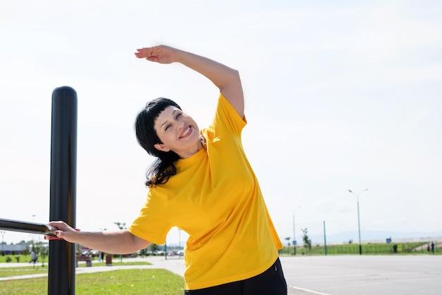 Senior vrouw doet zich het uitrekken buiten op het sportveld