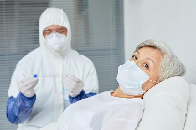 Senior vrouw dragen masker liggend op bed in de ziekenhuisafdeling met arts in beschermende uniform achter zitten