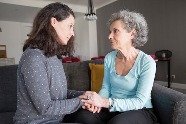 Senior vrouw en haar dochter chatten, kijken naar elkaar