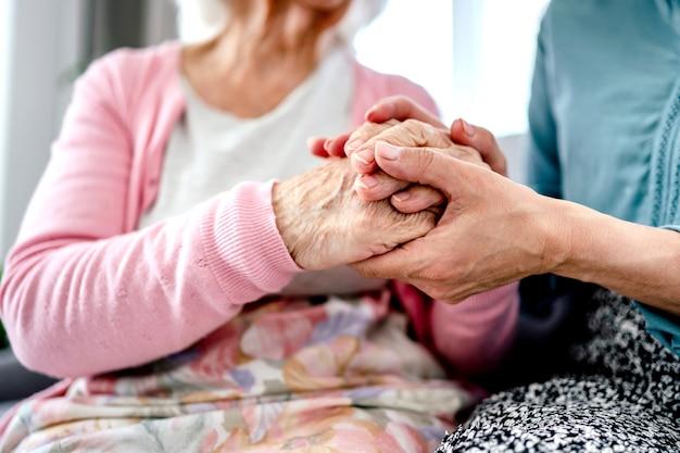 Senior vrouw en haar dochter hand in hand. oma met kleindochter familiemomenten samen