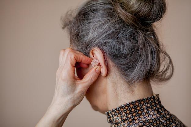 Senior vrouw gehoorapparaat invoegen in haar oren
