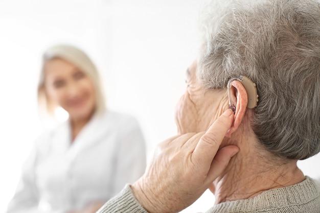 Senior vrouw gehoorapparaat op licht, close-up aanpassen