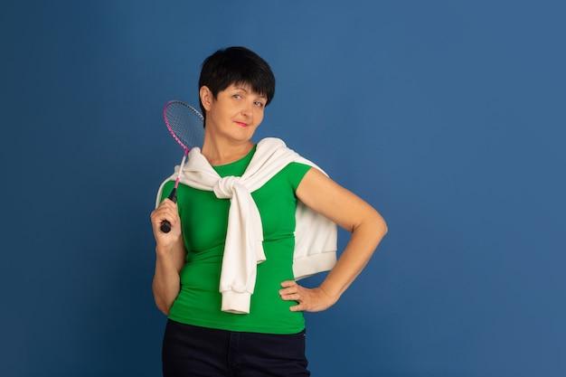 Senior vrouw geïsoleerd op blauwe achtergrond tech en vrolijke ouderen lifestyle concept