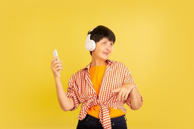 Senior vrouw geïsoleerd op geel. tech en vrolijk ouderen lifestyle concept