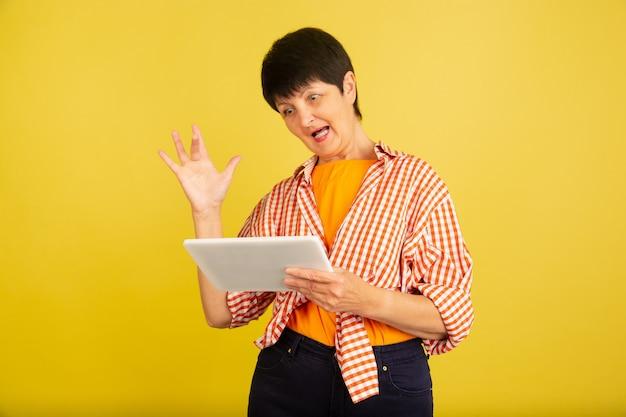 Senior vrouw geïsoleerd op gele achtergrond. tech en vrolijk ouderen lifestyle concept
