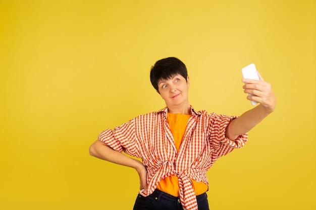 Senior vrouw geïsoleerd op gele achtergrond tech en vrolijke ouderen lifestyle concept