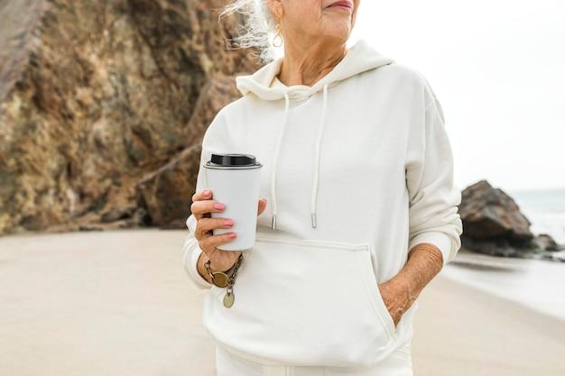 Senior vrouw geniet van haar ochtendkoffie op het strand