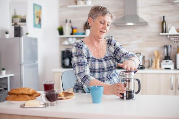 Senior vrouw genieten van een mok koffie van de franse pers tijdens het ontbijt. bejaarde in de ochtend genietend van vers bruin café espressokopje cafeïne uit vintage mok, filter ontspannen verfrissing