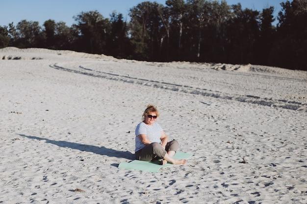 Senior vrouw gepensioneerde zitten in de natuur op zand