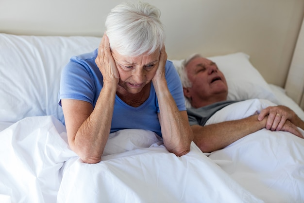 Senior vrouw gestoord met man snurken op bed in de slaapkamer