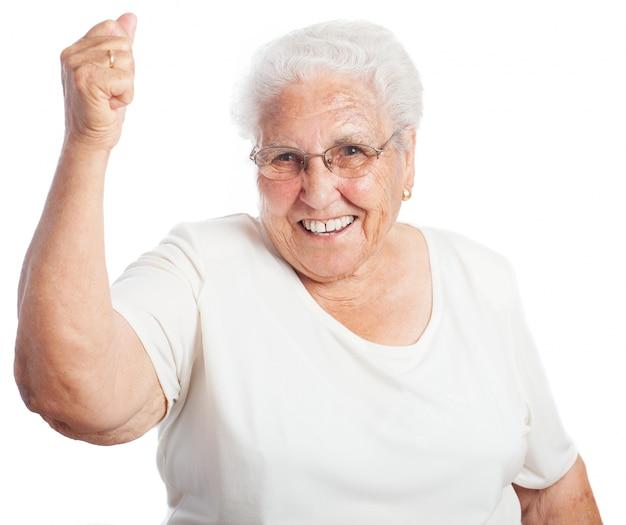 Senior vrouw glimlachend met een opgeheven vuist