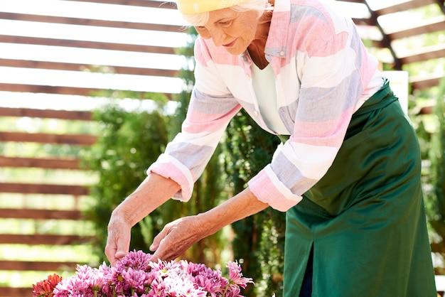 Senior vrouw groeiende bloemen