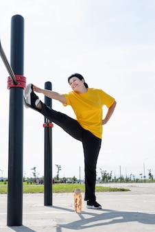 Senior vrouw haar benen buiten strekken op het sportveld