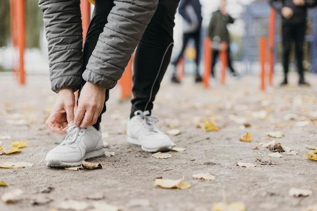 Senior vrouw haar schoenveters binden alvorens uit te werken