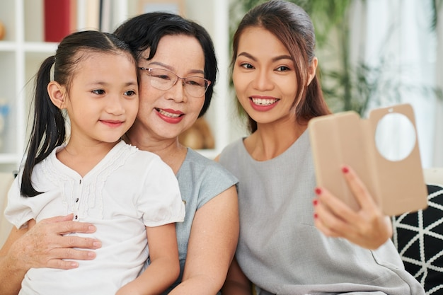 Senior vrouw, haar volwassen dochter en kleine kleindochter glimlachen en poseren voor selfie op smartphone