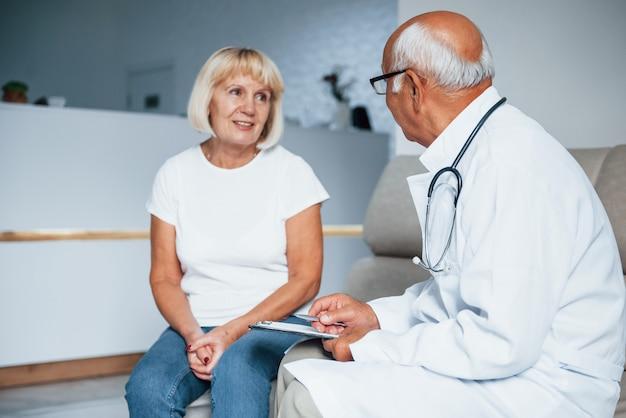Senior vrouw heeft overleg in de kliniek door de mannelijke arts.