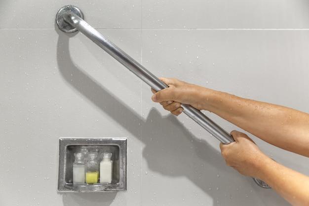 Senior vrouw houdt de leuning vast voor veiligheid in de badkamer