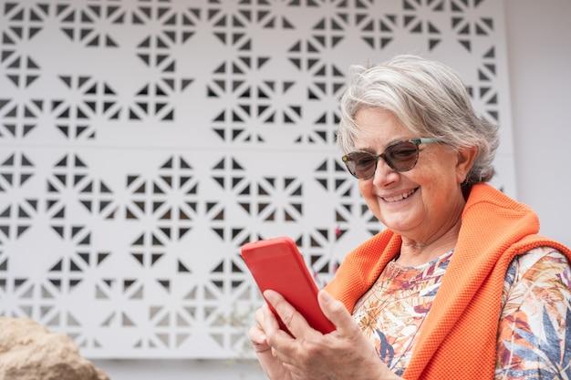 Senior vrouw in buitentuin glimlachend met behulp van draadloze technologie voor een bericht op mobiele telefoon, witte achtergrond