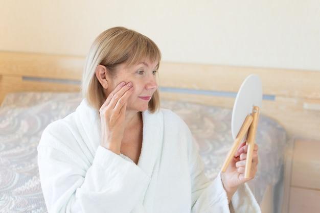 Senior vrouw in de slaapkamer anti-aging lotion toe te passen. kijkt in een cosmetische spiegel. concept anti-leeftijd, gezondheidszorg en cosmetologie, gepensioneerde, ouderdom
