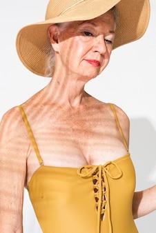 Senior vrouw in gele zomerkleding uit één stuk badpak