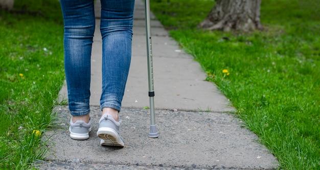 Senior vrouw in jeans loopt met riet wandelen buiten.